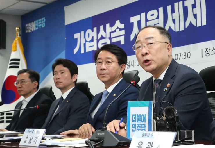 Finance Minister Hong Nam-ki, right, speaks about a new inheritance deductible tax system at the National Assembly in Seoul, Tuesday. Yonhap