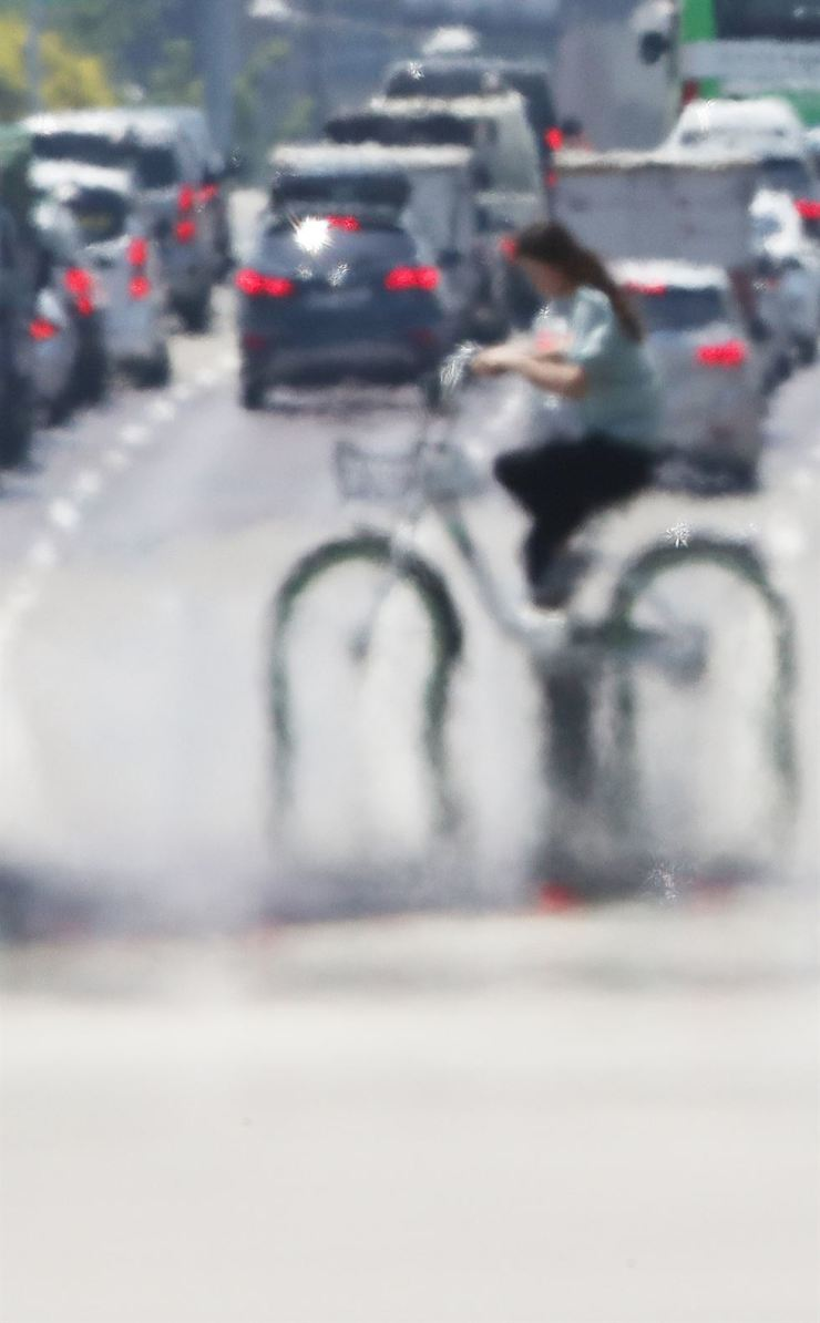 Haze rises from a road on Yeouido, Seoul, Monday, as a heat wave warning was issued in the capital city with the temperature rising to 32 degree Celsius. The hot weather is likely to continue for several days in central parts of the country. / Yonhap