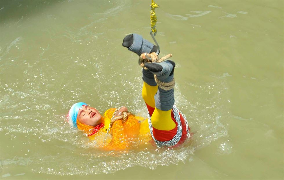 Chanchal Lahiri, a magician, sits on a boat before performing one of his tricks in the Hooghly river in Kolkata, India, June 16. Reuters