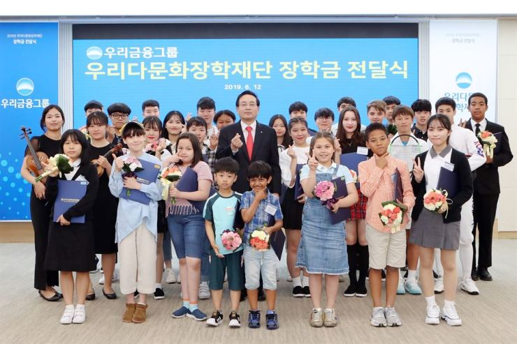 Woori Financial Group Chairman Sohn Tae-seung, center, poses with children of multiracial families at Woori Bank's charity event in Seoul, Wednesday. Woori gave scholarships worth 630 million won to 400 multiracial students. Courtesy of Woori Financial Group