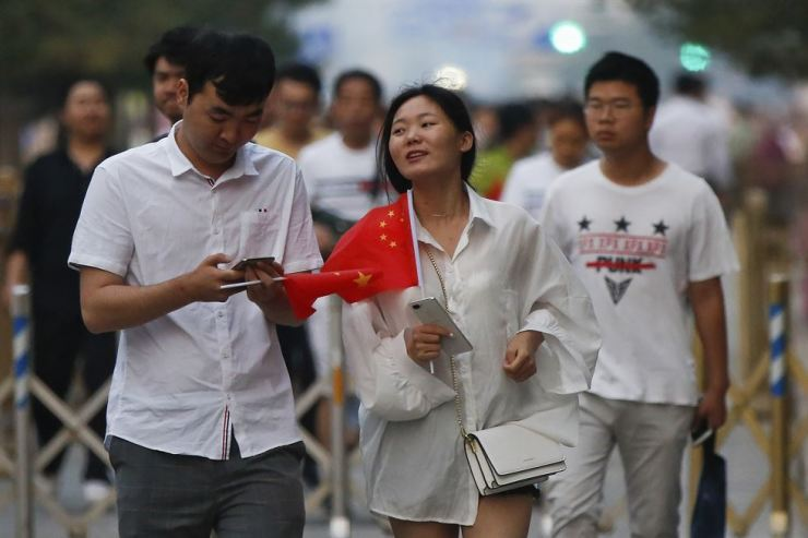 A Chinese couple hold Chinese national flags after attending the daily flag raising ceremony at Tiananmen Square on the 30th anniversary for the 1989 crackdown on pro-democracy protest in Beijing, Tuesday, June 4, 2019. AP-Yonhap