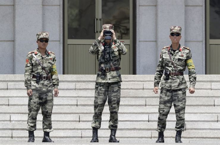 In this June 12 photo, North Korean soldiers look at the South side, seen during a press tour at the Panmunjom in the Demilitarized Zone, South Korea. AP