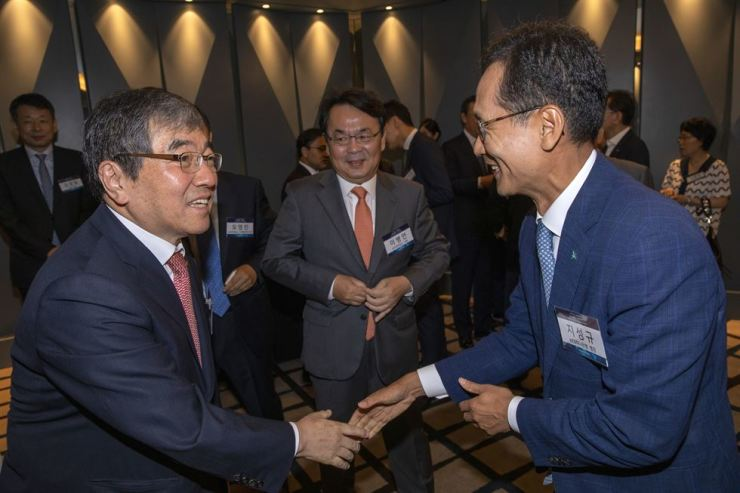 Financial Supervisory Service Governor Yoon Suk-heun shakes hands with KEB Hana Bank CEO Ji Sung-kyoo at The Korea Times' forum on digital transformation, held at the Plaza Hotel Seoul, Wednesday. / Korea Times photo by Shim Hyun-chul
