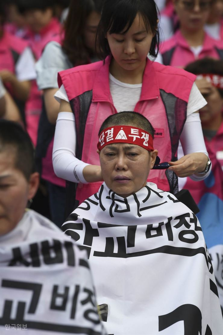 A temporary school worker has her head shaved, along with 99 other workers, during a protest in front of Cheong Wa Dae, Monday, calling on the Moon Jae-in administration to guarantee better job security by switching them to permanent positions. According to the Korean Confederation of Trade Unions, education workers account for over half of the 70,000 irregular workers in the public sector. / Korea Times photo by Hong Yoon-ki
