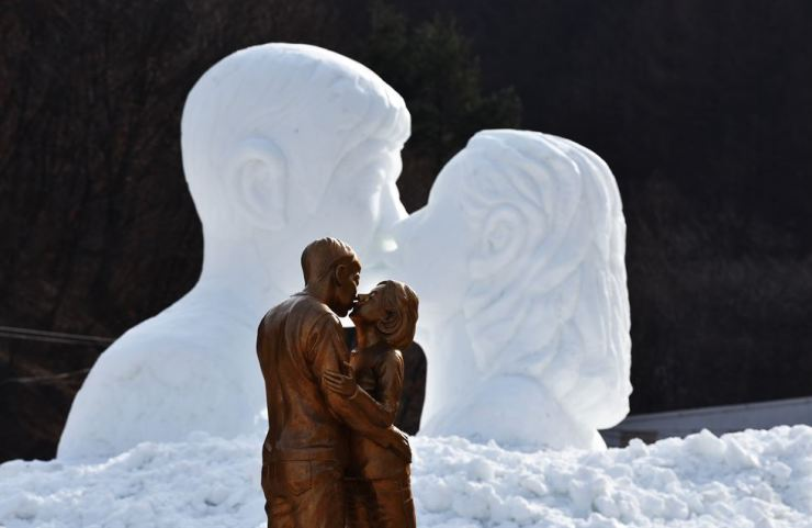 A statue and a snow sculpture that depicts a romantic scene between characters played by Song Joong-ki and Song Hye-kyo in the drama 'Descendants of the Sun' on display at a park in Taebaek, Gangwon Province, in this February 2018 photo. The two announced Thursday they would end 20 months of marriage. / Korea Times file
