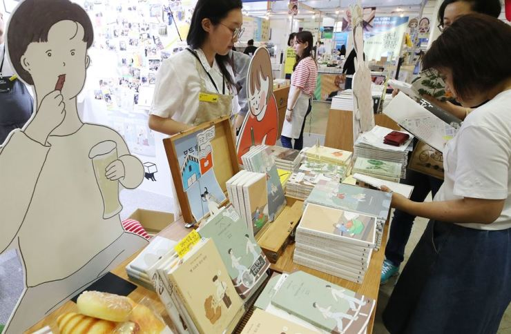 Visitors at this year's Seoul International Book Fair browse displayed books at COEX, southern Seoul, Wednesday. Yonhap