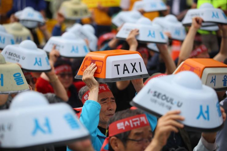 Taxi drivers hold top lights in a rally in front of the Ministry of Land, Infrastructure and Transport in Sejong, Wednesday, to urge the government to put a halt to ride-hailing services, including Tada, claiming the services are destroying the taxi industry. Yonhap