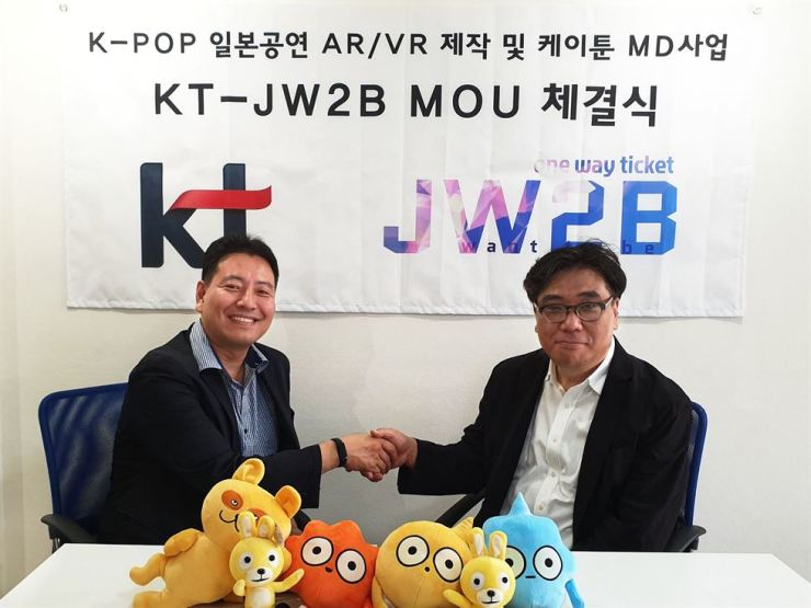 Jeon Dae-jin, left, a vice president who heads KT's content platform business department, shakes hands with JW2B CEO Koh Kwang-won in Tokyo, Thursday, after signing a business agreement to jointly push for VR and AR content business in Japan. JW2B is a Japan-based production agency that has managed performance activities of K-pop stars in Japan. Under the agreement, KT will offer video clips of K-pop stars' performances in Japan and distribute VR and AR content for 5G devices. / Courtesy of KT