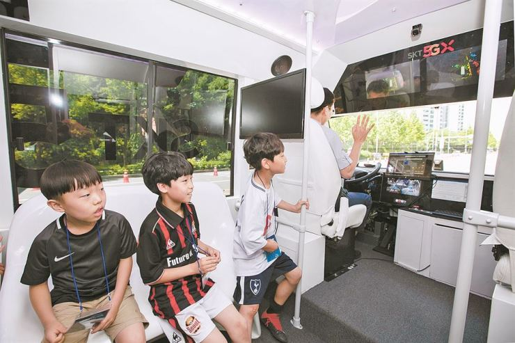 Elementary school students experience SK Telecom's 5G network-based self-driving bus during the Sangam Self-Driving Festival in Seoul, Saturday. / Courtesy of SK Telecom