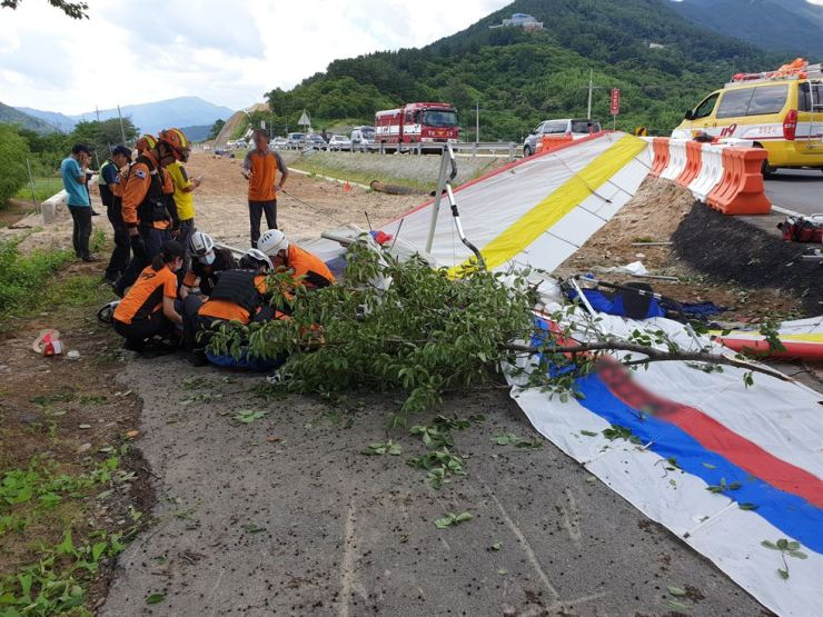 Rescue workers give emergency treatment after the two hang gliders collided at Hadong, South Gyeongsang Province, Sunday. Yonhap