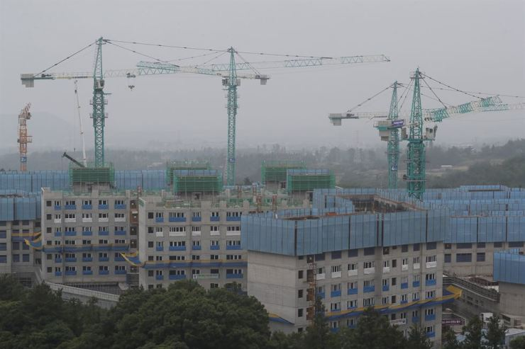Tower cranes sit idle at an apartment building construction site on Jeju Island, Tuesday, as crane workers went on strike. / Yonhap