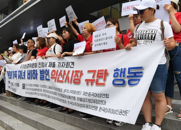 Multiethnic families and civic group members rally in front of the National Human Rights Commission building in Seoul, Friday, to condemn Mayor Chung Heon-yool of Iksan, North Jeolla Province, for his racist remarks about multiethnic children. In a speech last month, he called multiracial children 'hybrids.' / Korea Times photo by Hong Yoon-ki
