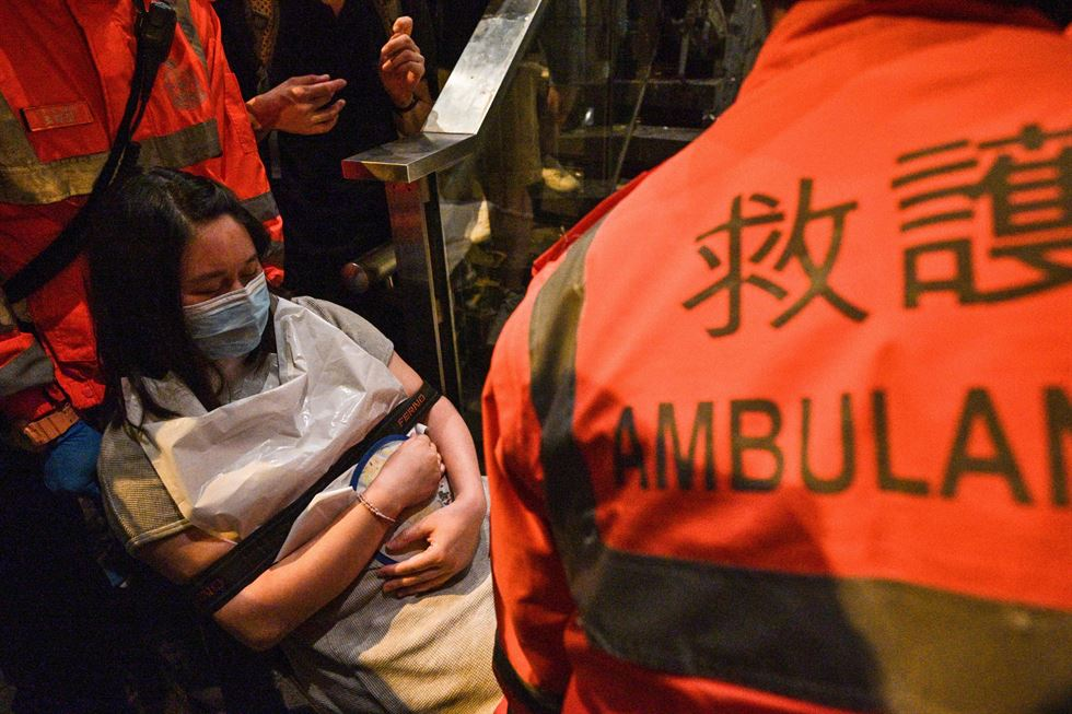 Paramedics assist a woman after taking her out of the police headquarters, which was surrounded by protesters in Hong Kong early on June 22. AFP-Yonhap