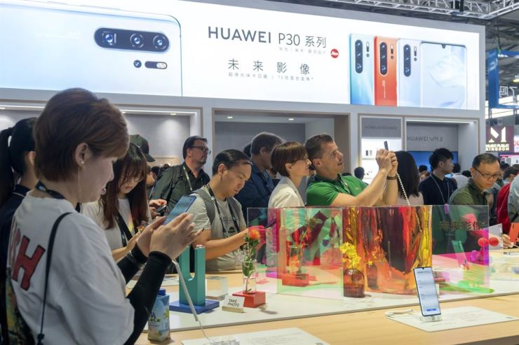 Visitors look at a display of smartphones from Chinese technology firm Huawei at the Consumer Electronics Show in Shanghai, June 11. AP-Yonhap
