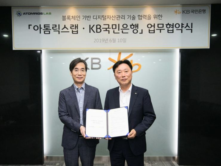 Lee Woo-yeol, right, head of KB Kookmin Bank's IT group, poses with startup Atomrigs Lab CEO Jung Woo-hyun at the bank's data center on Yeouido, Seoul, Tuesday. Both sides agreed to collaborate in developing a blockchain-based digital asset management business. Courtesy of KB Kookmin Bank