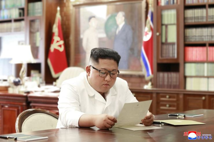 North Korean leader Kim Jong-un reads a letter sent from U.S. President Donald Trump at his office in this photo provided by the North's Korean Central News Agency, Sunday. Yonhap