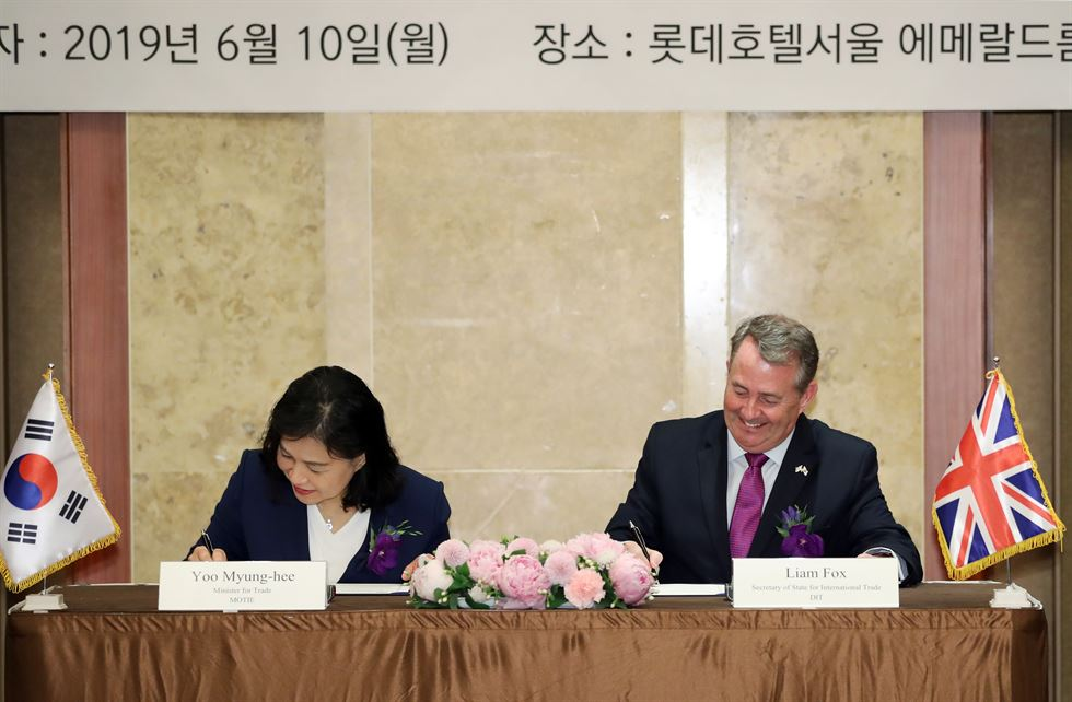 South Korean Trade Minister Yoo Myung-hee, left, and Liam Fox, the British Secretary of State for International Trade, enters a room at Lotte Hotel Seoul to sign a new South Korea-U.K. free trade agreement, June 10. Yonhap