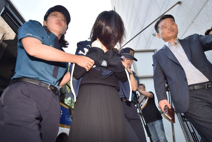 Police escort Koh Yu-jeong to the Jeju District Prosecutors' Office on Jeju Island, June 12. Korea Times file