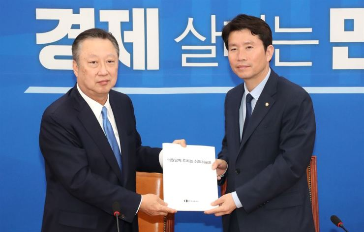 Korea Chamber of Commerce and Industry (KCCI) Chairman Park Yong-maan, left, hands over a copy of a KCCI report on bills to Rep. Lee In-young, floor leader of the ruling Democratic Party of Korea at the National Assembly, Monday. Yonhap