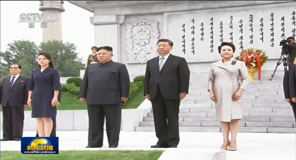 North Korean leader Kim Jong-un, left, and Chinese President Xi Jinping, left, greet the crowd before a mass gymnastic performance at the Rungrado 1st of May Stadium in Pyongyang, Thursday, during Xi's first day of a two-day trip to the North. / Xinhua-Yonhap