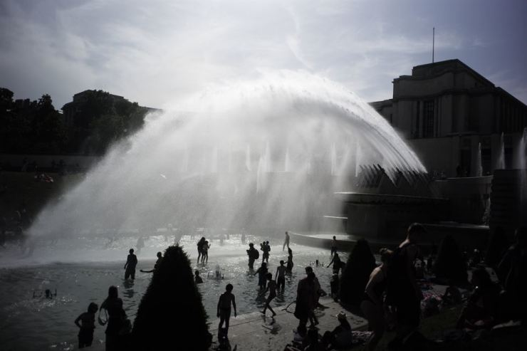 People play in the fountains of the Trocadero gardens in Paris, June 28. Schools are spraying kids with water and nursing homes are equipping the elderly with hydration sensors as France and other nations battle a record-setting heat wave baking much of Europe. AP