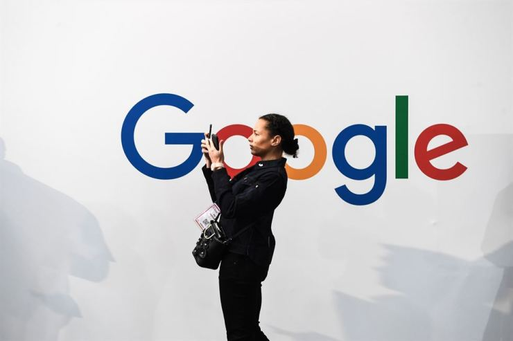 In this file photo taken on May 16, a woman takes a picture with two smartphones in front of the logo of the U.S. multinational technology and internet-related services company Google in Paris. AFP