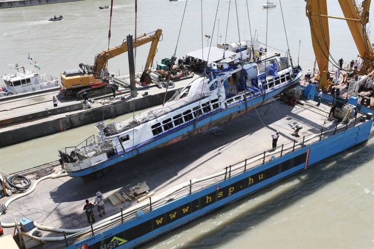 The sunken sightseeing boat Hableany is placed on a barge after being salvaged from the Danube River in Budapest, Tuesday, two weeks after its deadly sinking. Rescue workers recovered four more bodies from the ill-fated vessel, three of whom are believed to be Korean. The Hableany, which carried 33 South Korean passengers and two Hungarian crewmembers, sank on the Danube, May 29, after being hit by another larger boat, leaving seven survivors and 24 people dead with four still missing. Yonhap