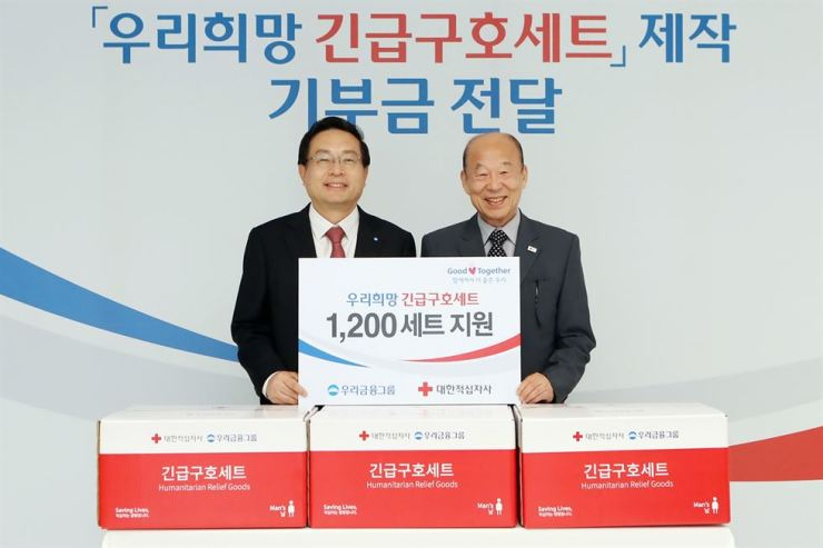 Woori Financial Group Chairman Sohn Tae-seung, left, stands with Korea Red Cross President Park Kyung-seo at the group's headquarters in Seoul, Monday. Woori Financial spent 100 million won to provide 1,200 relief goods kits to the Korea Red Cross. Courtesy of Woori Financial Group