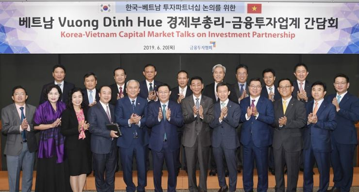 Korea Financial Investment Association Chairman Kwon Yong-won, front row seventh from left, applauds with Vietnam's Deputy Prime Minister Vuong Dinh Hue, front row sixth from left, and CEOs of securities firms during their partnership event at the association's office on Yeouido, Seoul, Thursday. / Courtesy of Korea Financial Investment Association