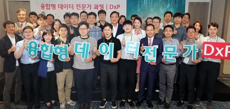 Hana Financial Group Chairman Kim Jung-tai, fifth from right in the second row, and KEB Hana Bank CEO Ji Sung-kyoo, fourth from right in the first row, pose with young workers selected to take a data specialist nurturing program at a hotel in Seoul, June 10. Courtesy of Hana Financial Group