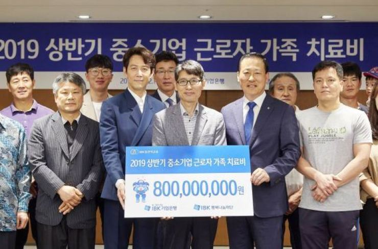 Industrial Bank of Korea (IBK) CEO Kim Do-jin, front row second from right, holds a promotional banner with actor Lee Jung-jae, second from left, at the bank's head branch in central Seoul, Wednesday. IBK donated 800 million won on the day to support 161 family members of small- and medium-sized enterprise workers in their medical expenses. The bank has donated a total 41.5 billion won through its charity foundation since 2006. / Courtesy of Industrial Bank of Korea
