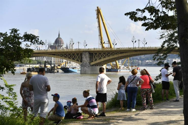 People watch as a 200-ton lift capacity crane maneuvers into position near the Margaret bridge on the Danube river, June 10, preparing to salvage to sunken shipwreck from the scene of a deadly boat accident in Budapest, Hungary. MTI via AP
