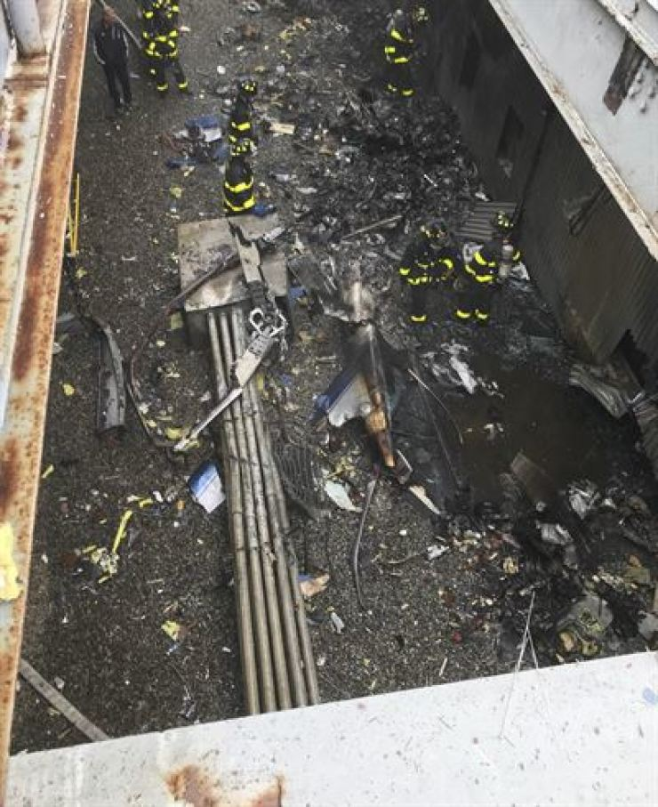 This photo released by the New York City Fire Department shows damage caused by a helicopter crash, south of Central Park in New York, June 10. The crash that killed the pilot and occurred near Times Square and Trump Tower shook the 750-foot (229-meter) AXA Equitable building sparked a fire and forced office workers to flee on elevators and down stairs, witnesses and officials said. FDNY via AP