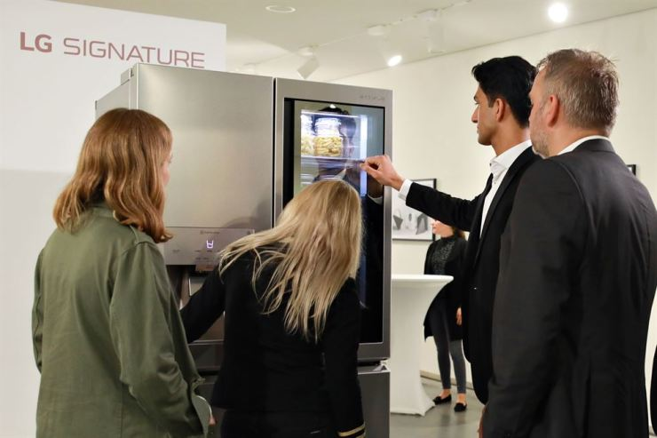 An LG Electronics employee explains features of the company's SIGNATURE refrigerator to visitors during a showcase event at Astrup Fearnley Museet museum in Oslo, Norway, Thursday. / Courtesy of LG Electronics