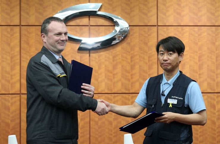 Renault Samsung CEO Dominique Signora, left, shakes hands with the company's union leader Park Joong-kyu, after signing an agreement over wages and other working conditions at Renault Samsung's plant in Busan, Monday. Yonhap