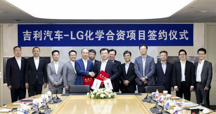 Kim Jong-hyun, right, president of LG Chem's energy solutions business, shakes hands with Geely Vice President Feng Ching Feng, after the two companies agreed to set up a joint venture for EV batteries, at the latter's research center in Ningbo, China, Wednesday. / Courtesy of LG Chem
