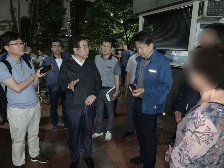 Seoul Mayor Park Won-soon, second from left, visits an apartment complex in western Seoul, Friday, after a reddish contamination in tap water was reported. / Courtesy of Seoul Metropolitan Government