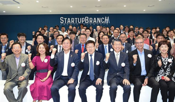 Industry Minister Sung Yoon-mo, third from left in the front row, and KITA CEO Kim Young-ju, fourth from left in the front row, pose with entrepreneurs and industry officials at the opening of the Startup Branch at COEX, Tuesday. Courtesy of KITA