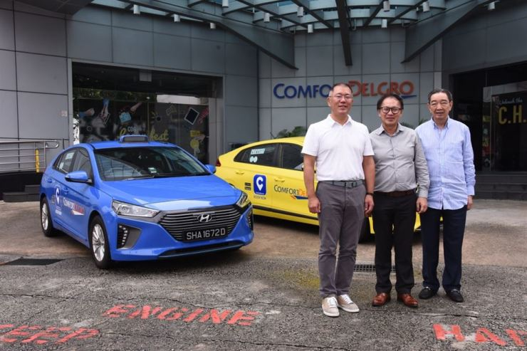 Hyundai Motor Group Executive Vice Chairman Chung Euisun, left, and ComfortDelGro CEO Yang Ban Seng, center, pose for a photo in front of ComfortDelGro headquarters in Singapore, June 19. / Courtesy of Hyundai Motor