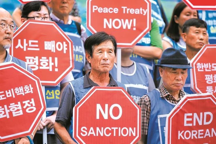 Members of the Solidarity for Peace and Reunification of Korea hold signs that reads 'No Sanctions' and 'Peace Treaty Now' during a protest against U.S. President Donald Trump's visit to Korea, at the Sejong Center for the Performing Arts in Seoul, Sunday. / Korea Times photo by Choi Won-suk
