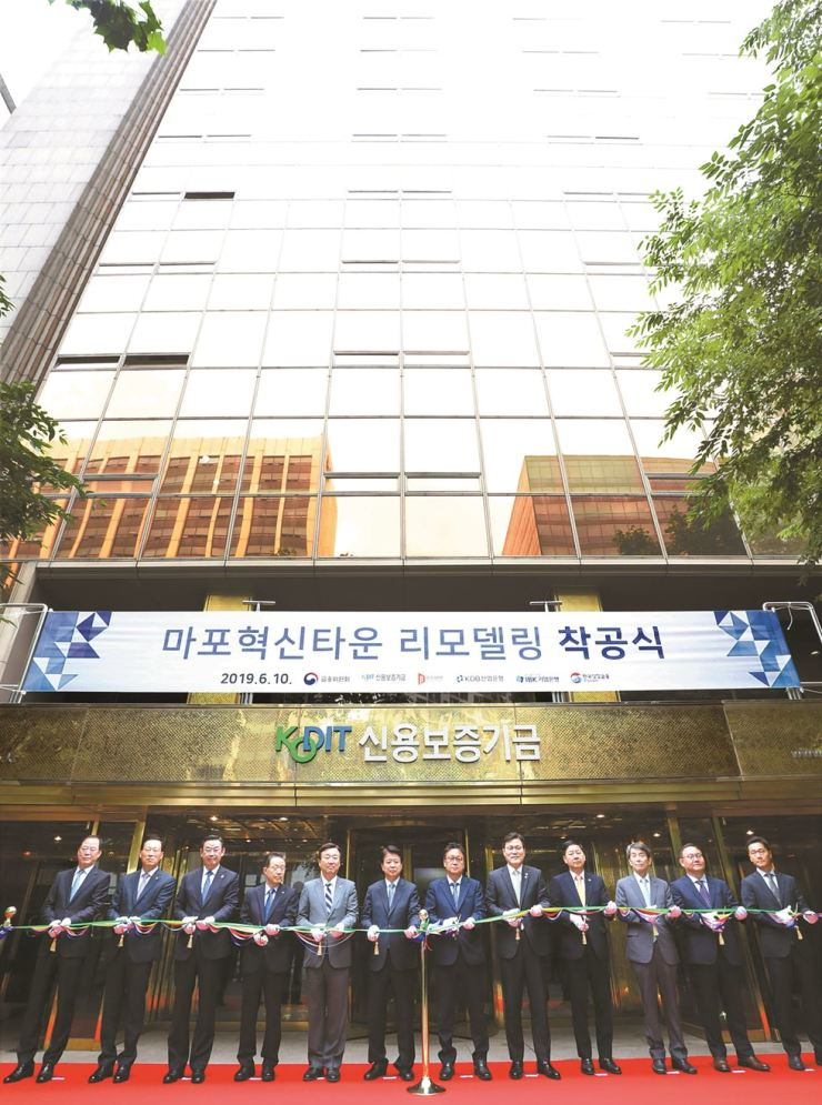 Financial Services Commission Chairman Choi Jong-ku, fifth from right, cuts a ribbon with Korea Federation of Banks Chairman Kim Tae-young, third from left, and Korea Credit Guarantee Fund (KODIT) Chairman Yoon Dae-hee, fourth from left, and other guests at a ceremony to build the Mapo Innovation Town in western Seoul, June 19. The financial regulator is creating the facility to provide a platform to support promising startups with innovation-led business models. It is located inside the old KODIT building. Courtesy of KODIT