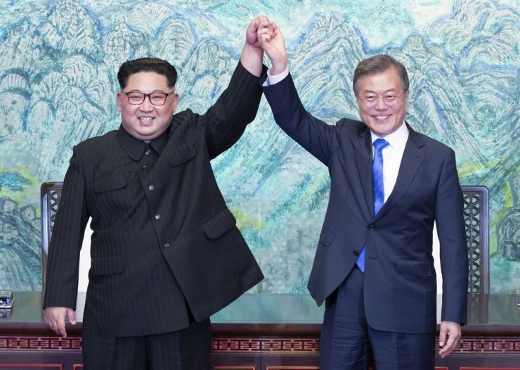 In this April 27, 2018, file photo, North Korean leader Kim Jong-un, left, and President Moon Jae-in raise their hands after signing on a joint statement at the border village of Panmunjeom in the South Korean side of the Demilitarized Zone. AP-Yonhap