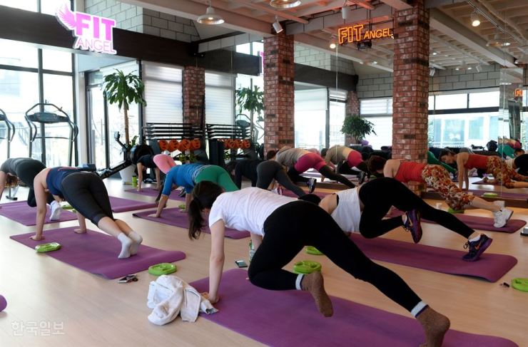 People work out at a fitness club in Seoul, in this 2017 photo. Many workers begin to spend free time in the evening exercising after implementation of the 52-hour workweek system. / Korea Times file