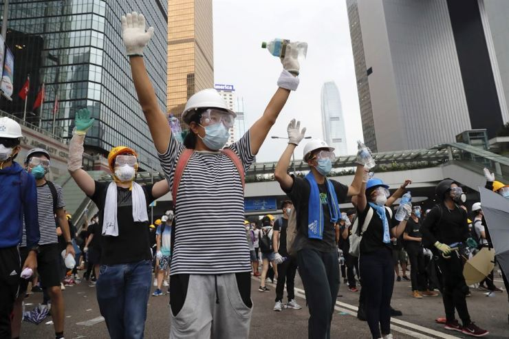 In this June 12 photo, demonstrators raise their hands near the Legislative Council in Hong Kong. AP