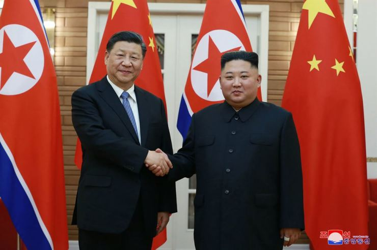 In this June 20 photo provided by the North Korean government, North Korean leader Kim Jong-un, right, shakes hands with Chinese President Xi Jinping at Kumsusan guest house in Pyongyang. KCNA via AP