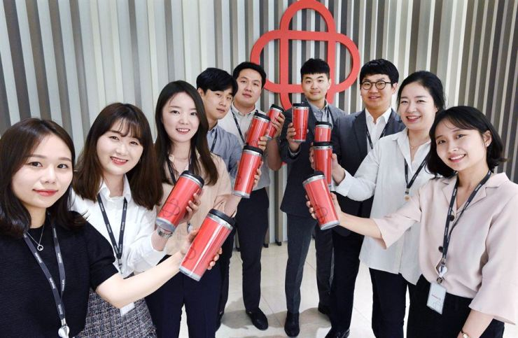 Homeplus employees pose with tumblers to mark World Environment Day on June 5 and raise awareness on sustainability at the company's headquarters in Seoul, Tuesday. Courtesy of Homeplus