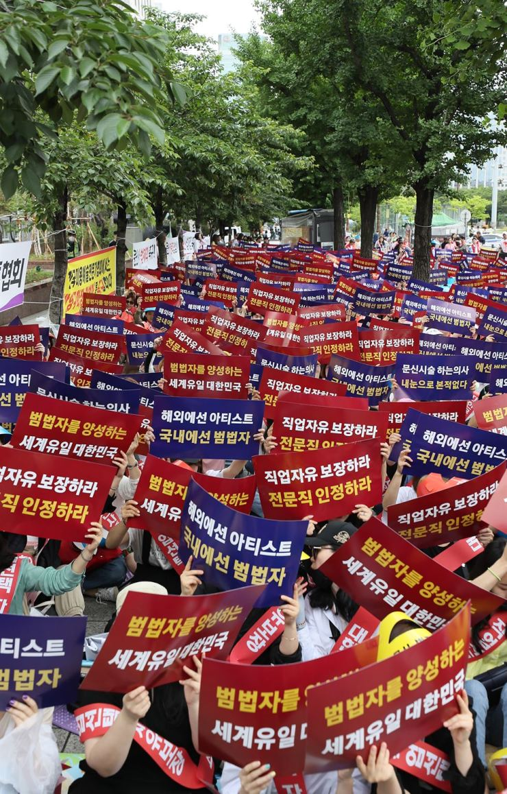 Hundreds of tattooists rally in front of the National Assembly on Yeouido in Seoul, Monday, calling on the government to recognize tattooing as a separate profession and legalize tattooing by non-doctors. Under the current law, tattooing is classified as a medical procedure, so it is illegal for a person without a medical license to make a tattoo. / Yonhap