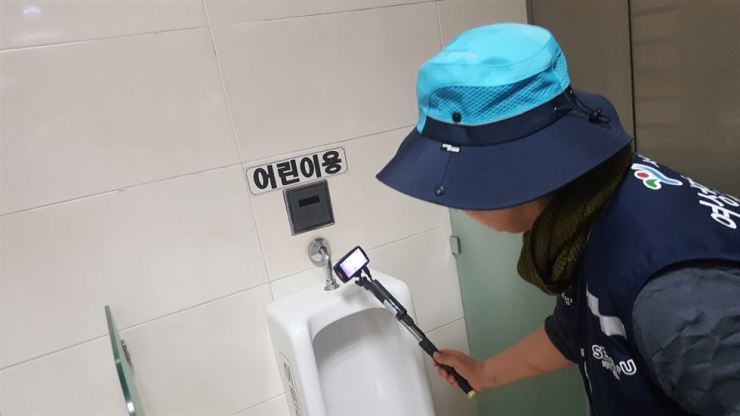 An inspector inspects a public toilet to check for the possible installation of a hidden camera in central Seoul in this April 24 photo. Korea Times file