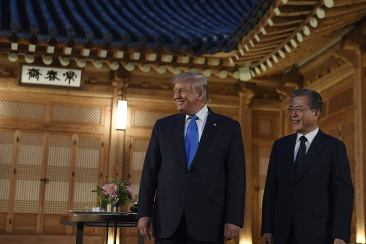 President Moon Jae-in, right, and U.S. President Donald Trump smile during their meeting at the tea house on the grounds of the Blue House in Seoul, South Korea, Saturday. AP