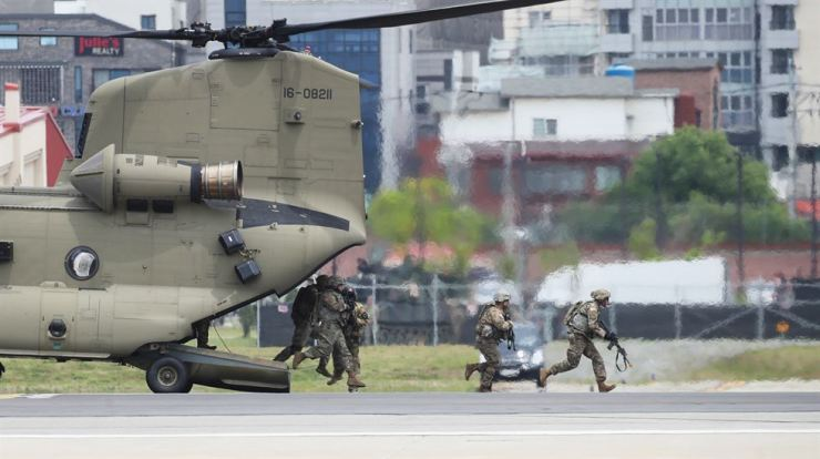 Soldiers of the U.S. Eighth Army, which is stationed at the U.S. Forces Korea (USKF) Camp Humphreys base in Pyeongtaek, Gyeonggi Province, exit a helicopter during a combat training demonstration at an event at the base to mark the 75th anniversary of its foundation, last Saturday. Yonhap